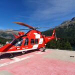 Engadine, St. Moritz, Swiss Air Rescue Rega Helicopter on Klinik Gut landing Pad with a view on Muottas Muragl, Badrutt's Palace Hotel Tower, St. Moritz Lake